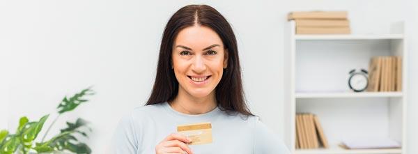 quanto ganha um terapeuta holístico? mulher sorrindo satisfeita com cartão de crédito
